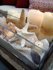 "This sea-inspired centerpiece is easy to make and can be used all year round. ""A rustic wooden tray provides the base for the rectangular glass vase filled with sand, candles and a variety of seashells,"" Katrina Giles of Seaside Interiors says. Add vibrant shells and starfish for an extra boost of summer hues."